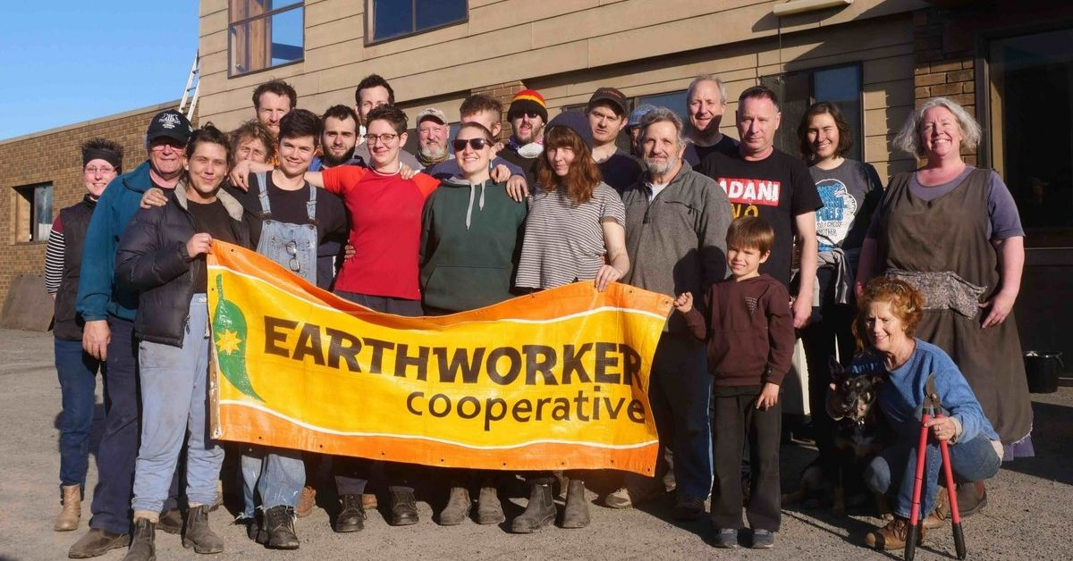 The Earthworker team with a banner