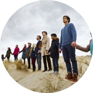 People in a line holding hands across a sand dune