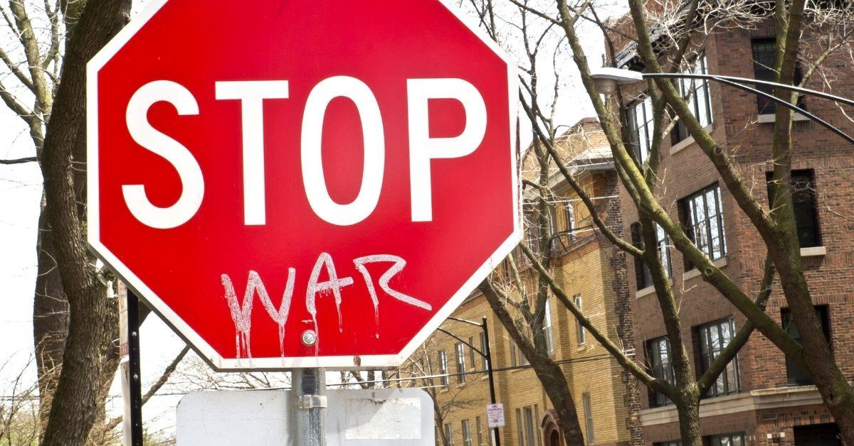 Stop sign with sprayed work - war