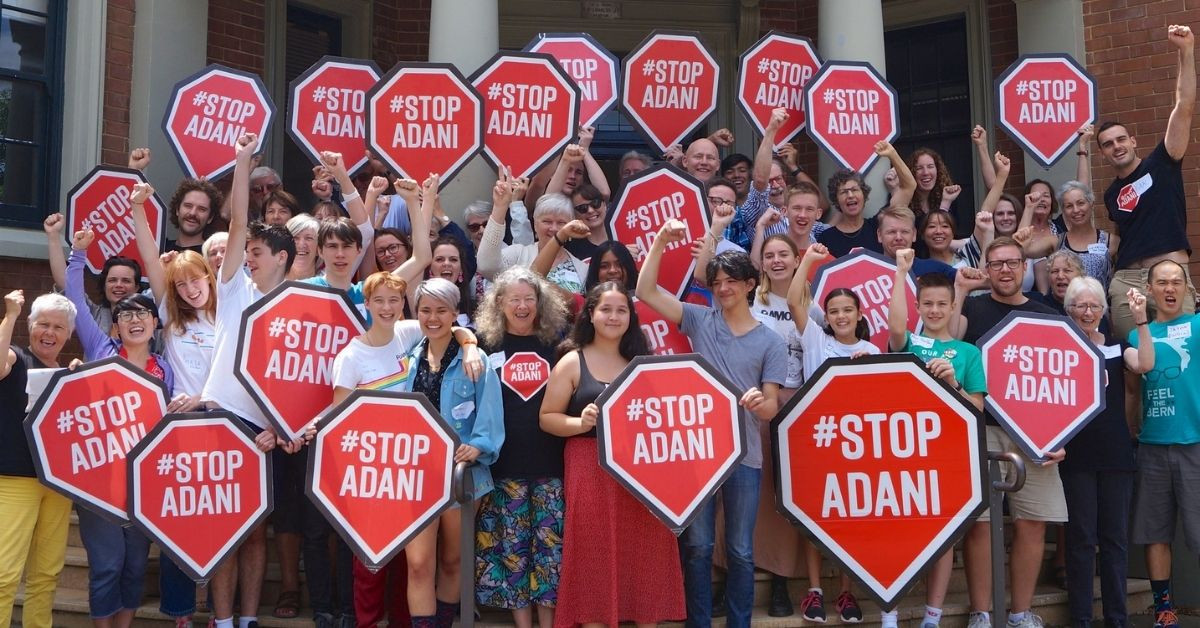Lots of people with Stop Adani signs