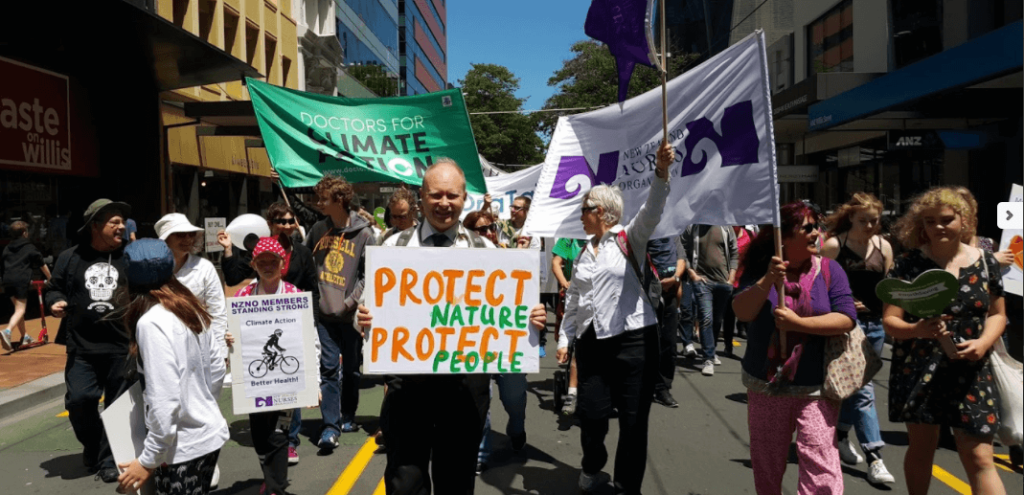 "Persona with placard that reads ""protect nature, protect people"" walks in climate rally"