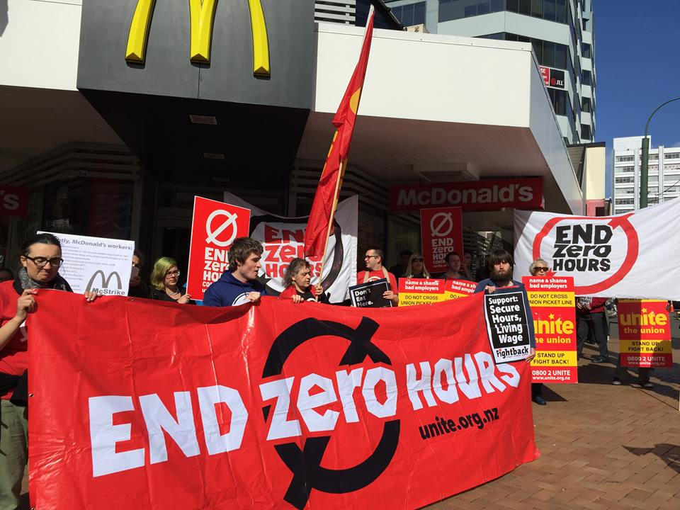 Unite members protest outside a McDonalds Restaurant. They stand holding a red banner with the words \
