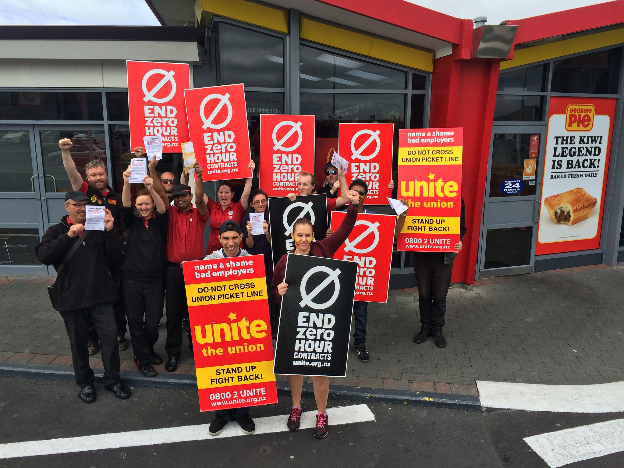 Workers outside a McDonalds Restaurant holding End Zero Hours placards