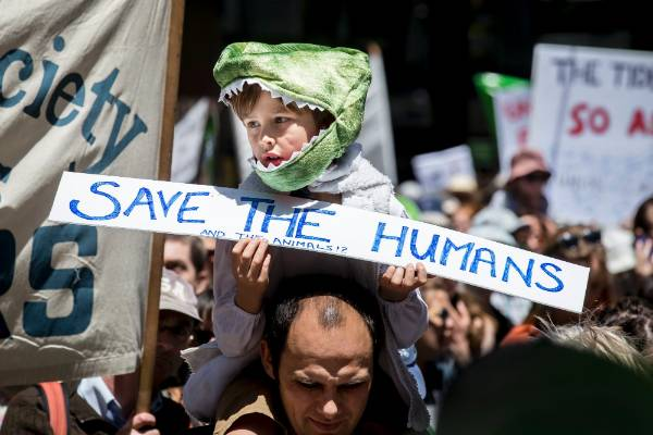 Child on fathers shoulders wearing an animal suit and carrying a sign saying \