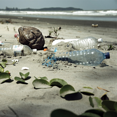 Plastic bottles and debris on a sandy beach.
