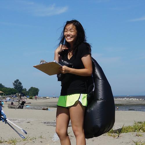 Fraser Riverkeeper Volunteer holding beach cleanup tools.