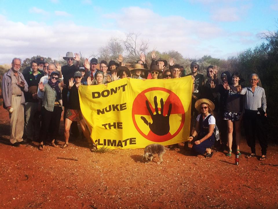 About 30 people standing in front of sand dunes in Woomera holding a banner that says 'Don't Nuke the Climate'