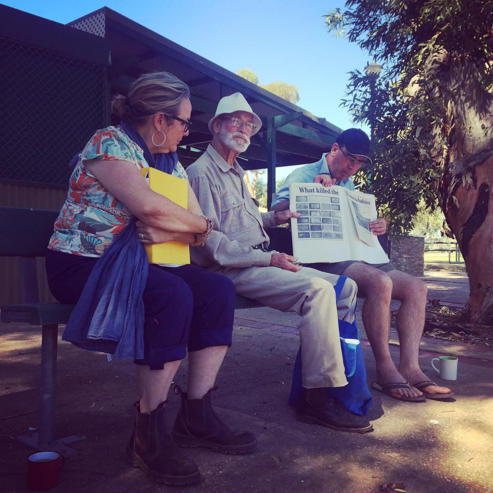 Dimity Hawkins (a middle aged woman), Avon Hudson (a older man) and Jim Green (a middle aged man) sitting on a park bench giving a talk. Avon is speaking and Jim is holding newspaper clippings.