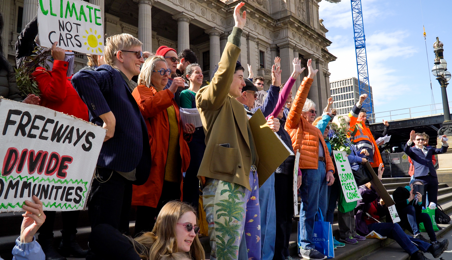 A group of people dressed in colourful clothes standing on Parliament steps with their hands in the air