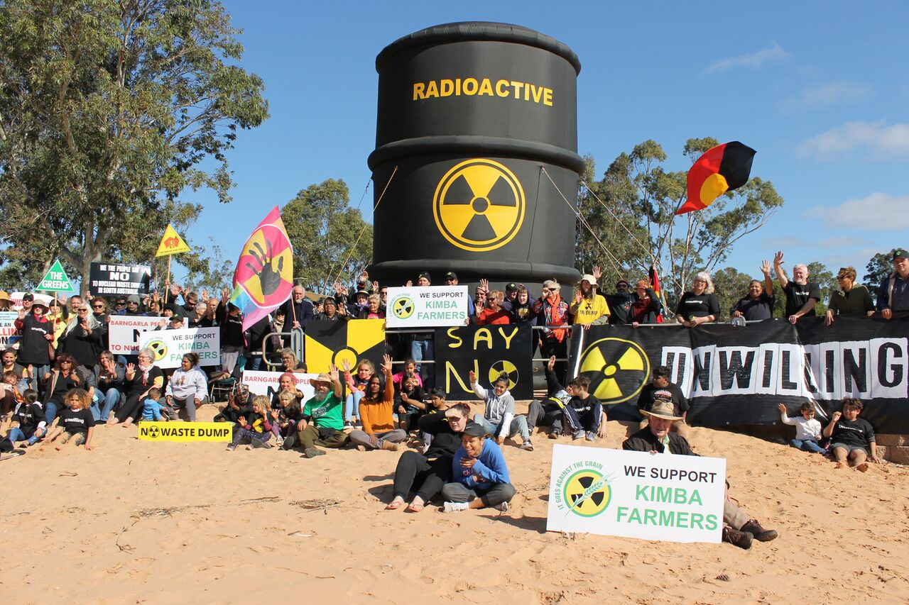 Large group of people with protest signs and flags in front of huge blow up waste barrel