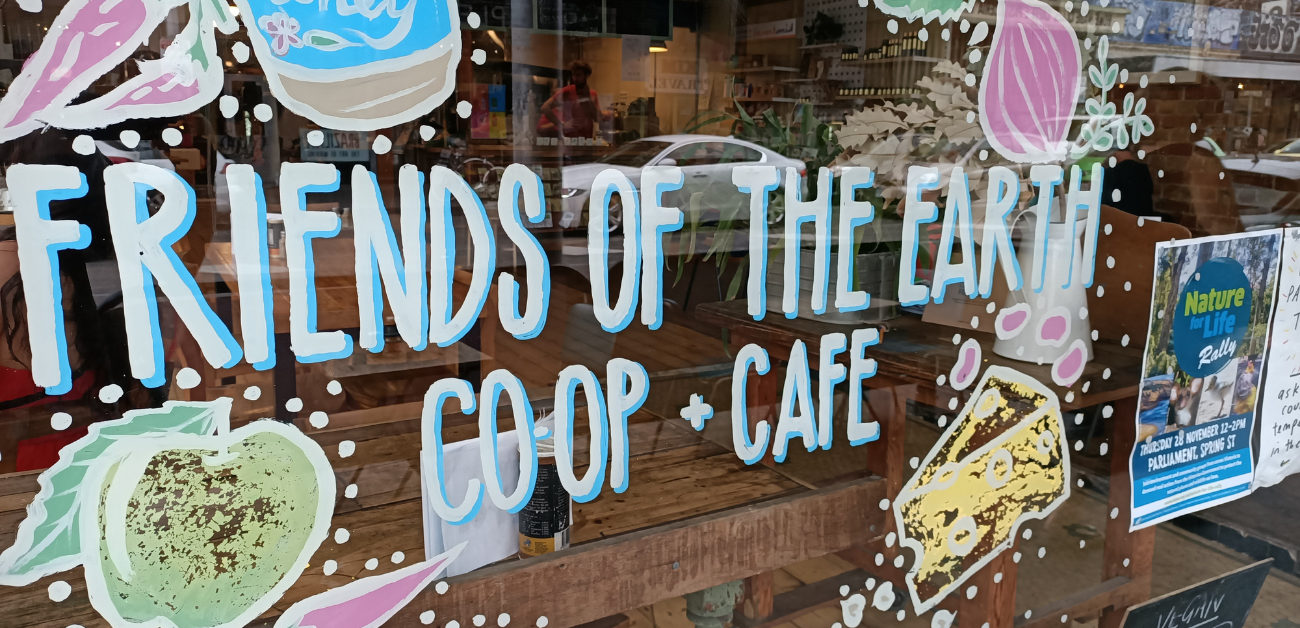 The front window of the Food Coop and Cafe with a hand written sign saying Friends of the Earth Food Co-op and Cafe