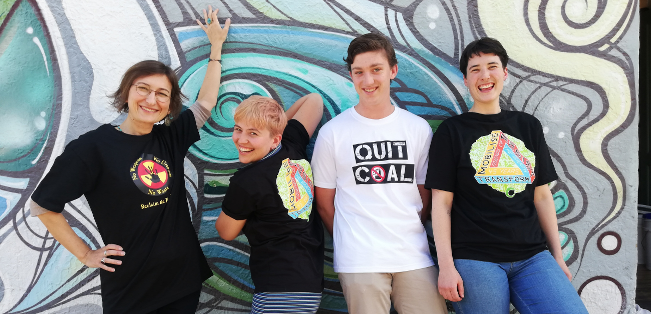 Four people in Friends of the Earth shirts stand in front of a graffitied wall