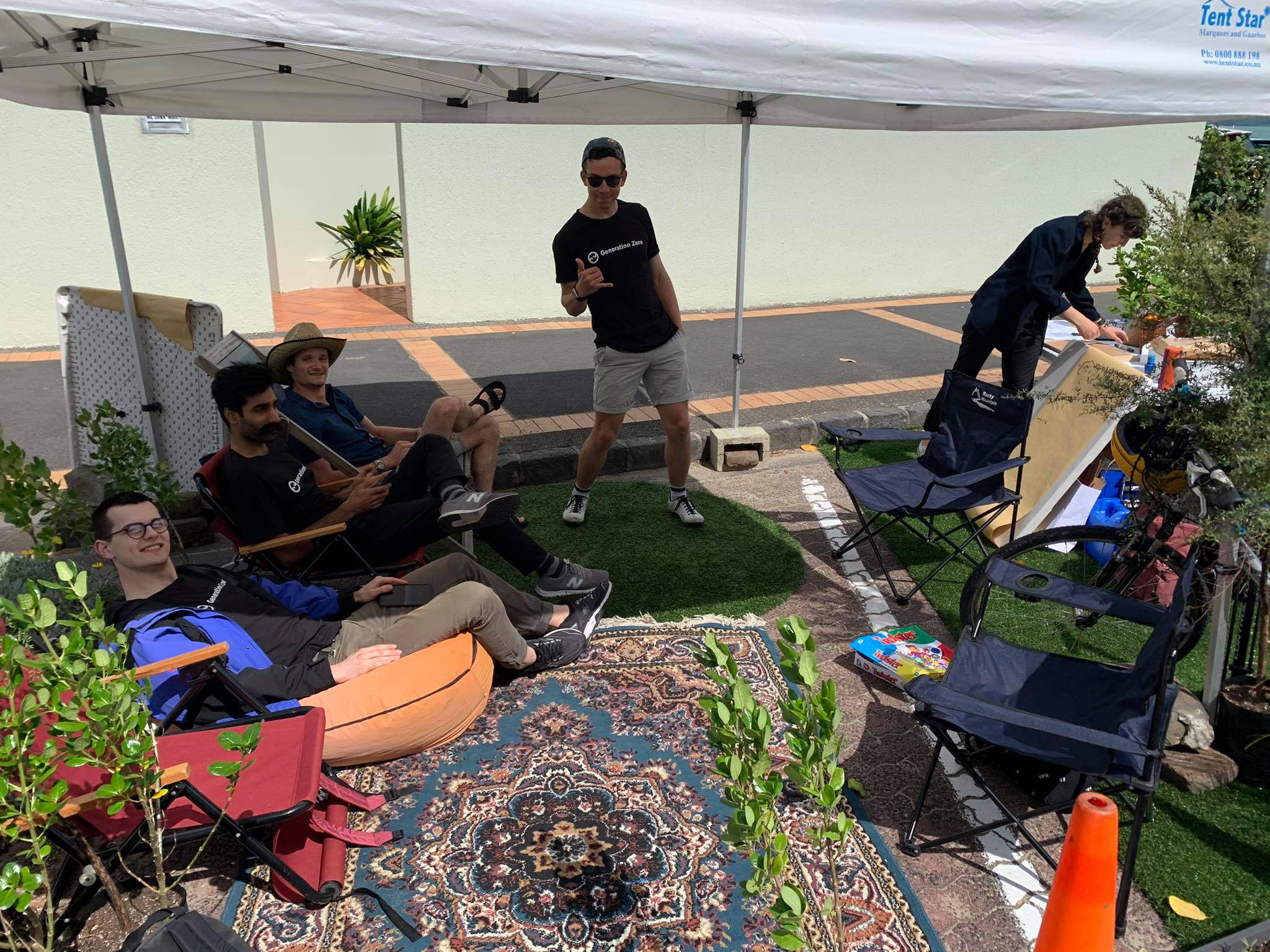 A carpark covered in a rug and turf with people lounging in beanbags and chairs under the shade of a marquee. There are also plants and roadcones