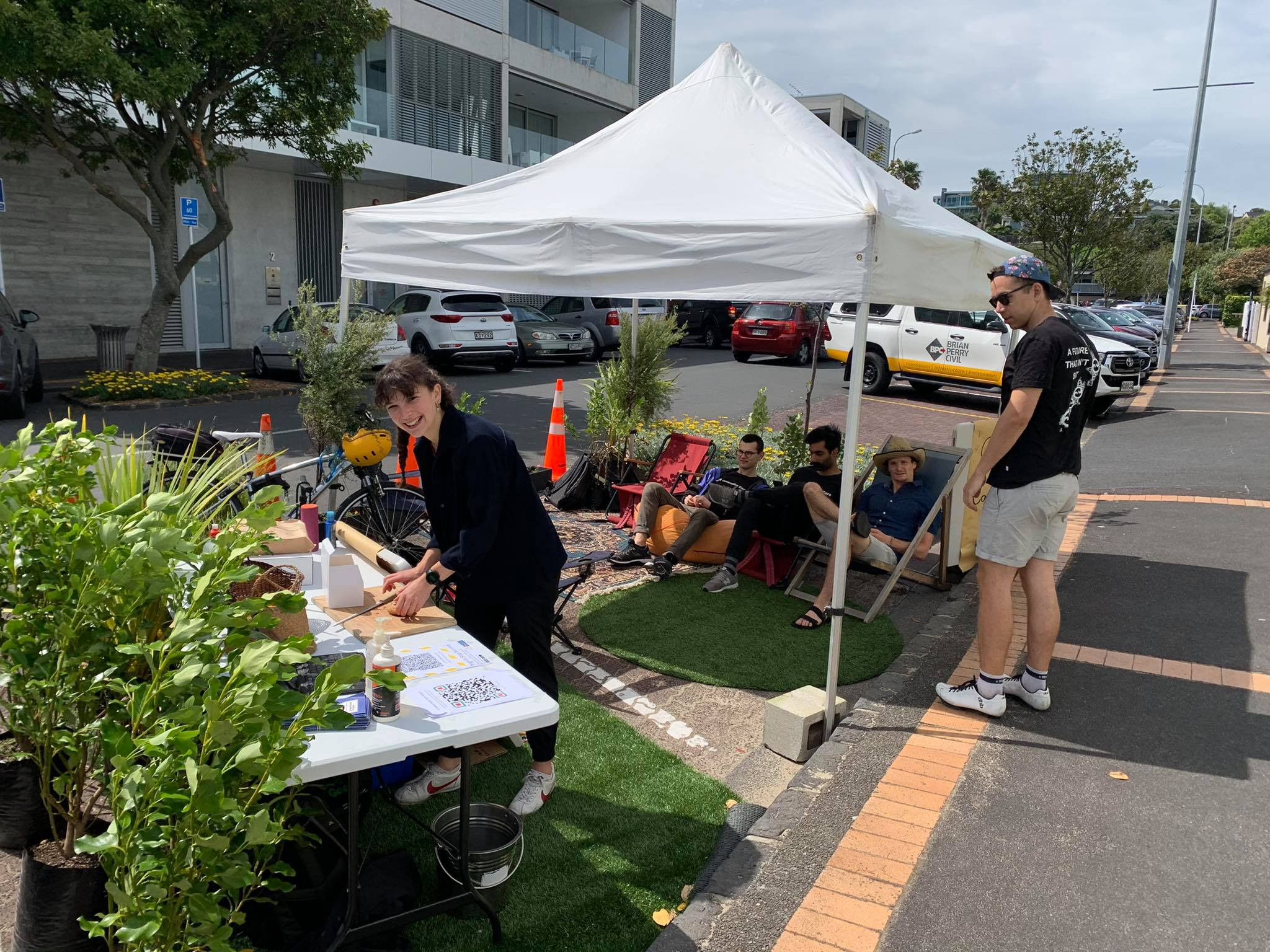 A few carparks on the side of a road are covered in turf, plants, tables, seating area and a marquee with people interacting in the space.