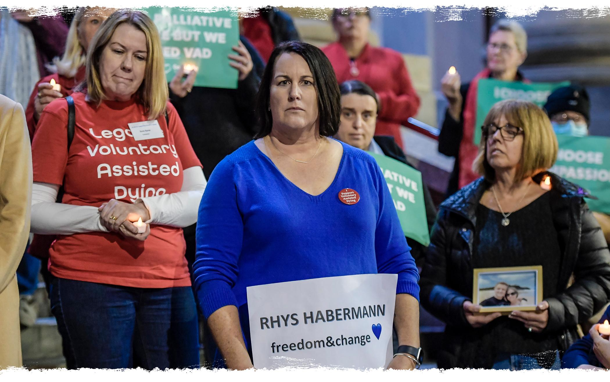 Liz Habermann hold a sign reading 'Rhys Habermann, freedom & change.'