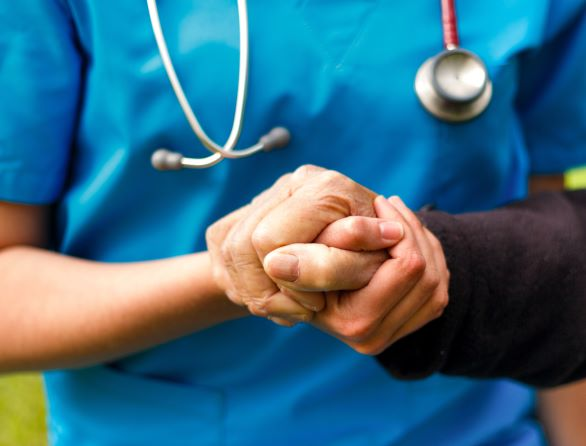 Doctors hands holding patinet's hands
