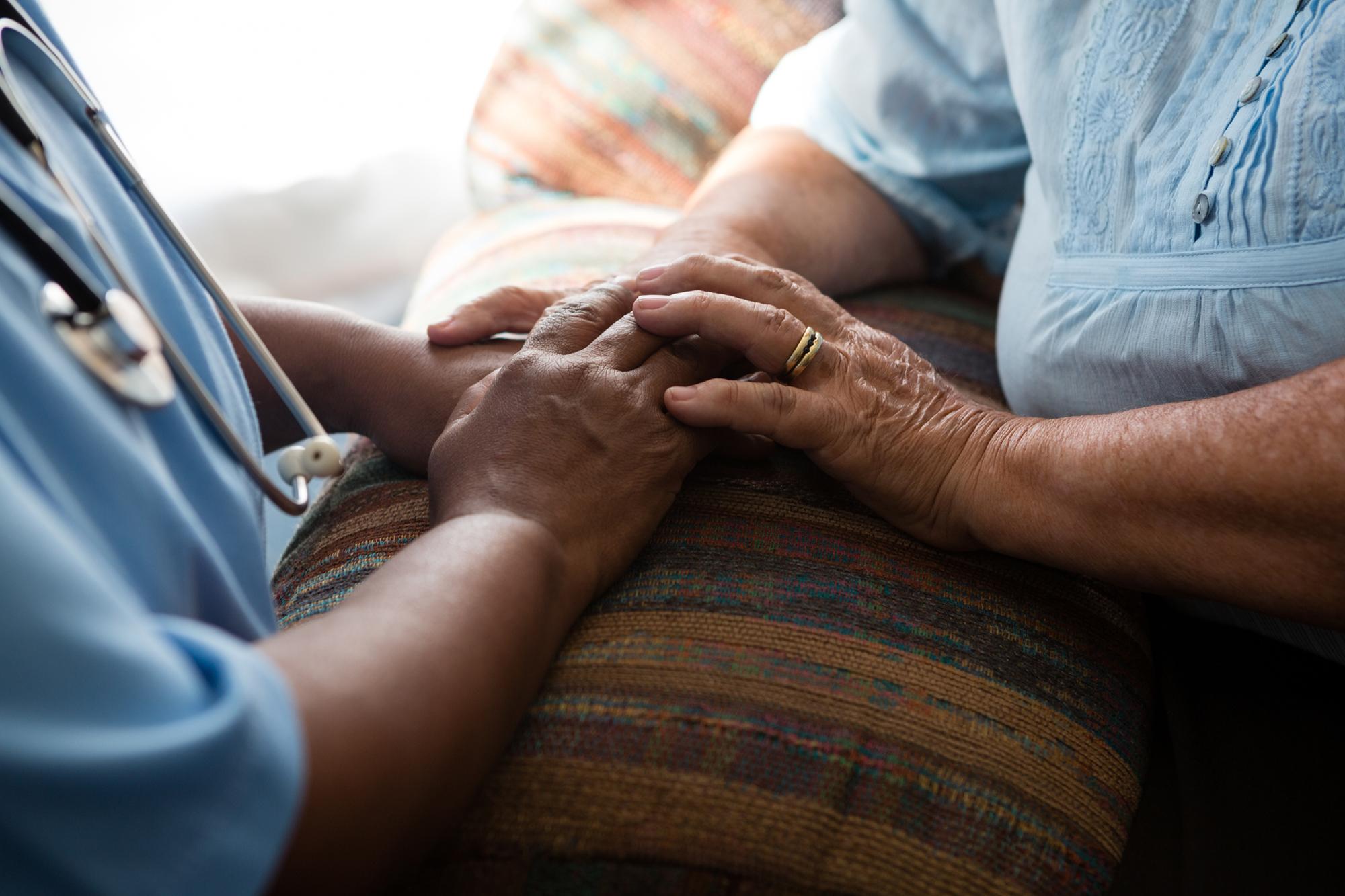 Nurse holds patients hands.