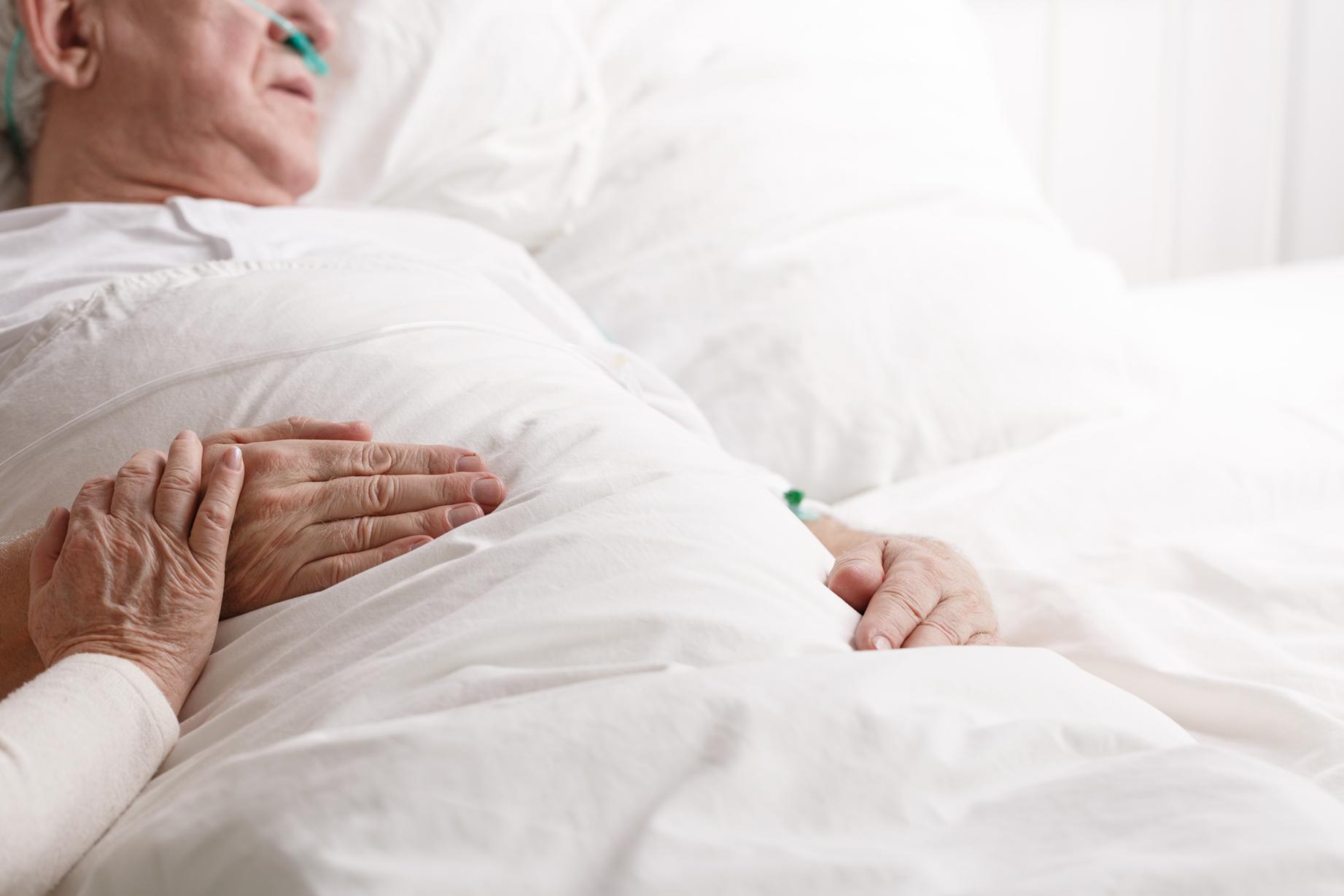 Patient lies in hospital bed.
