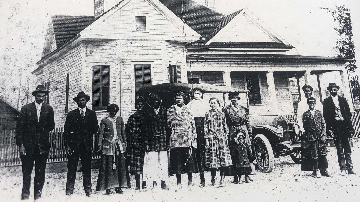 Members of the new communities farm stand outside a building
