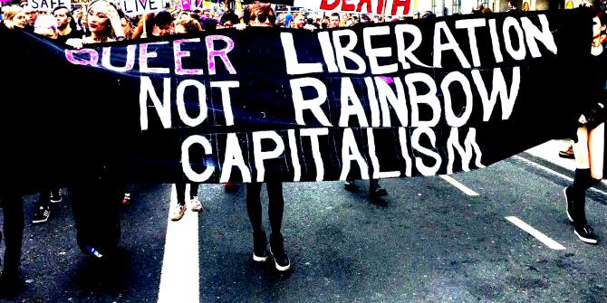people holding up a banner in a parade that reads queer liberation not rainbow capitalism