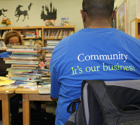 A volunteer from Deloitte helps level books in the Tubman Elementary library