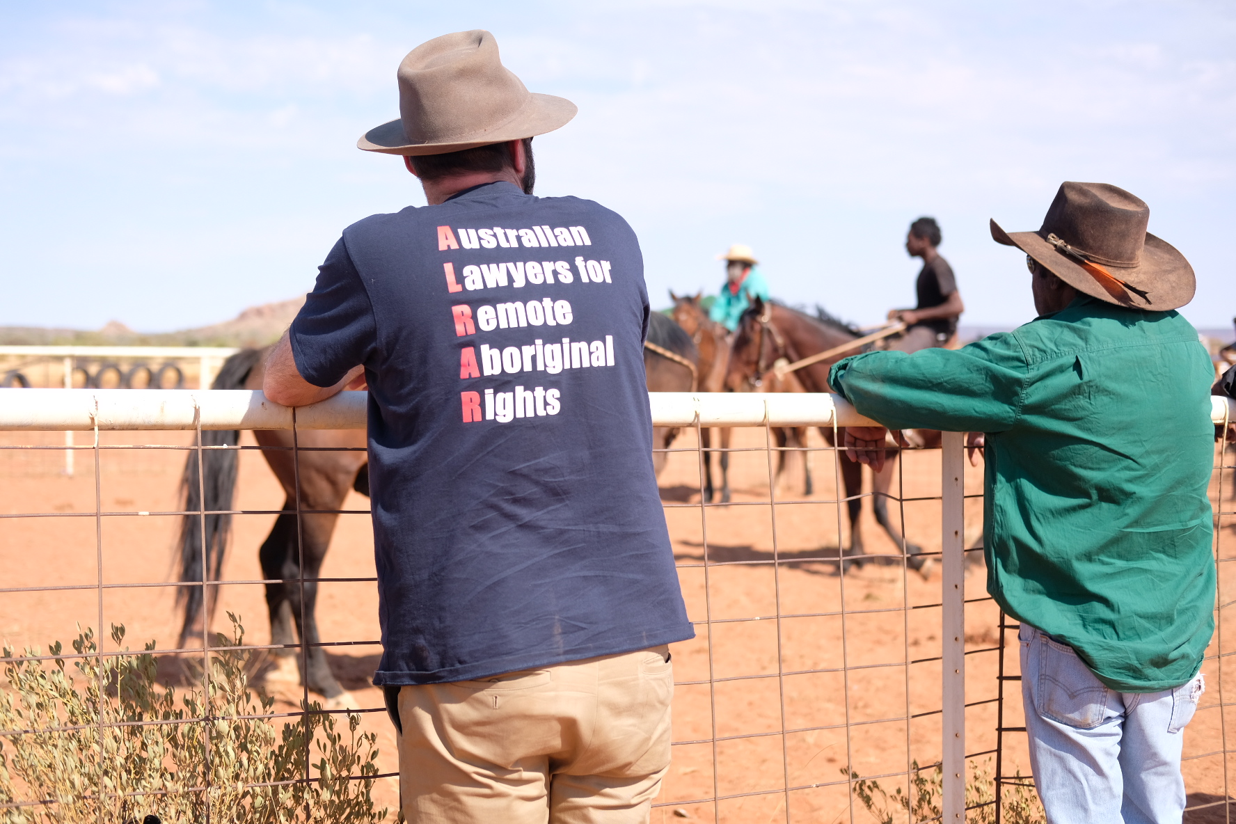 A lawyer from  the Australian Lawyers for Remote Aboriginal Rights leans against a fence watching a horse race in Santa Teresa.