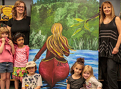 Photo of Katherine Laco and Susan Murray with students and murals