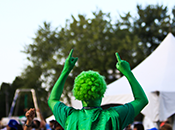 Photo of Harvest Picnic performer clad in all green, pointing to sky