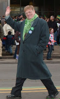 Alex White walking in a parade in a long coat with a green scarf on, waving to the crowd.