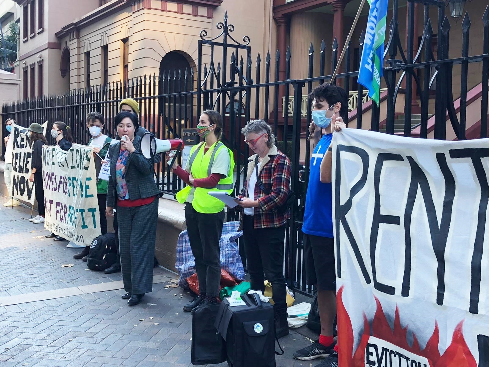 Jenny speaking into a megaphone whilst 8 other protesters hold signs about rent relief outside NSW Parliament.