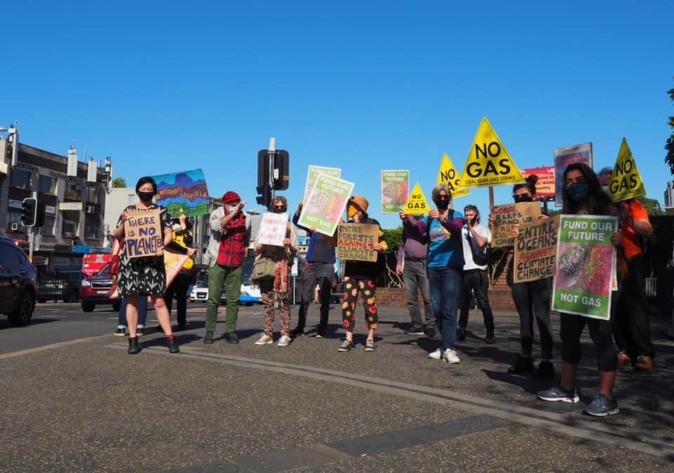 Jenny on the street with a group of approx 12 people holding climate action related signs and wearing masks, for a climate strike event.