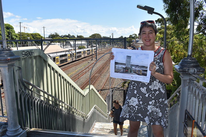 Jenny Leong MP pictured on the stairs at Petersham Station holding an image of the proposed upgrades.