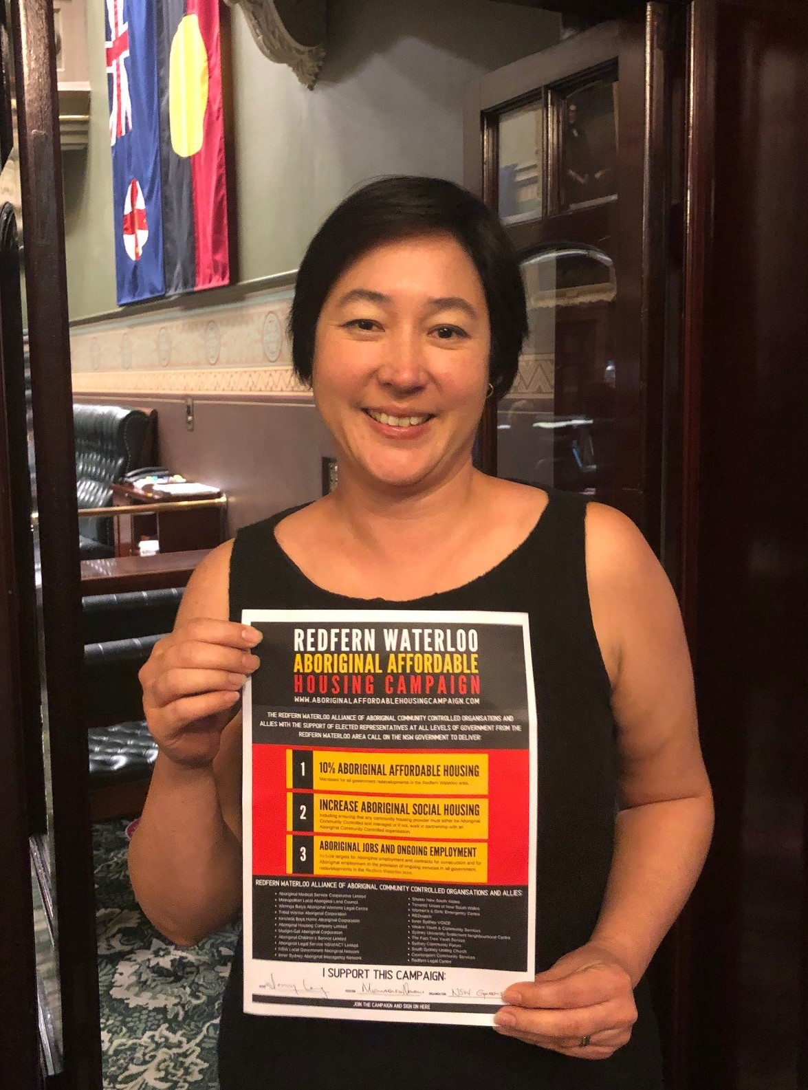 Jenny Leong MP holding the Redfern Waterloo Aboriginal Affordable Housing Campaign pledge.
