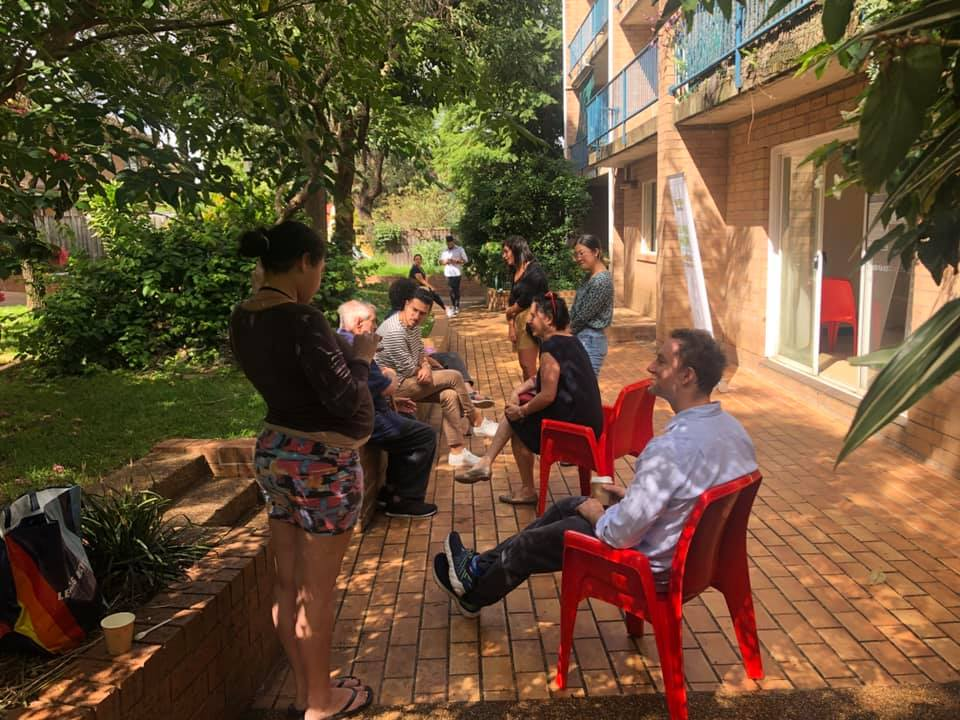 Photo at Alice St public housing, of people sitting outside.