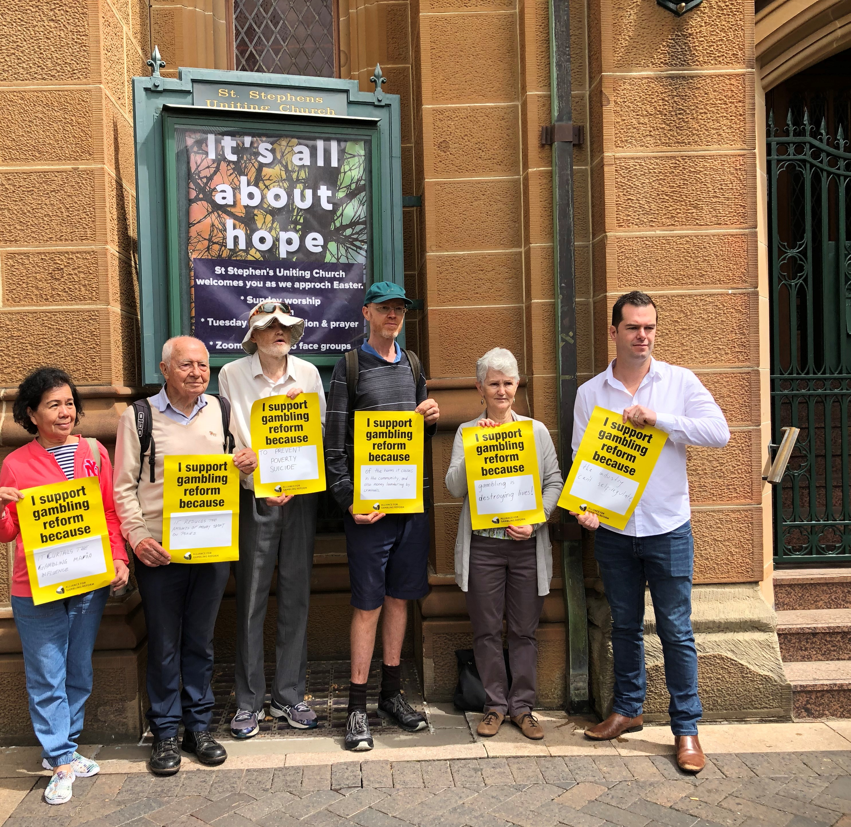 """A group of people holding posters stating """"I support gambling reform"""" in front of a church sign saying """"It's all about hope"""""""