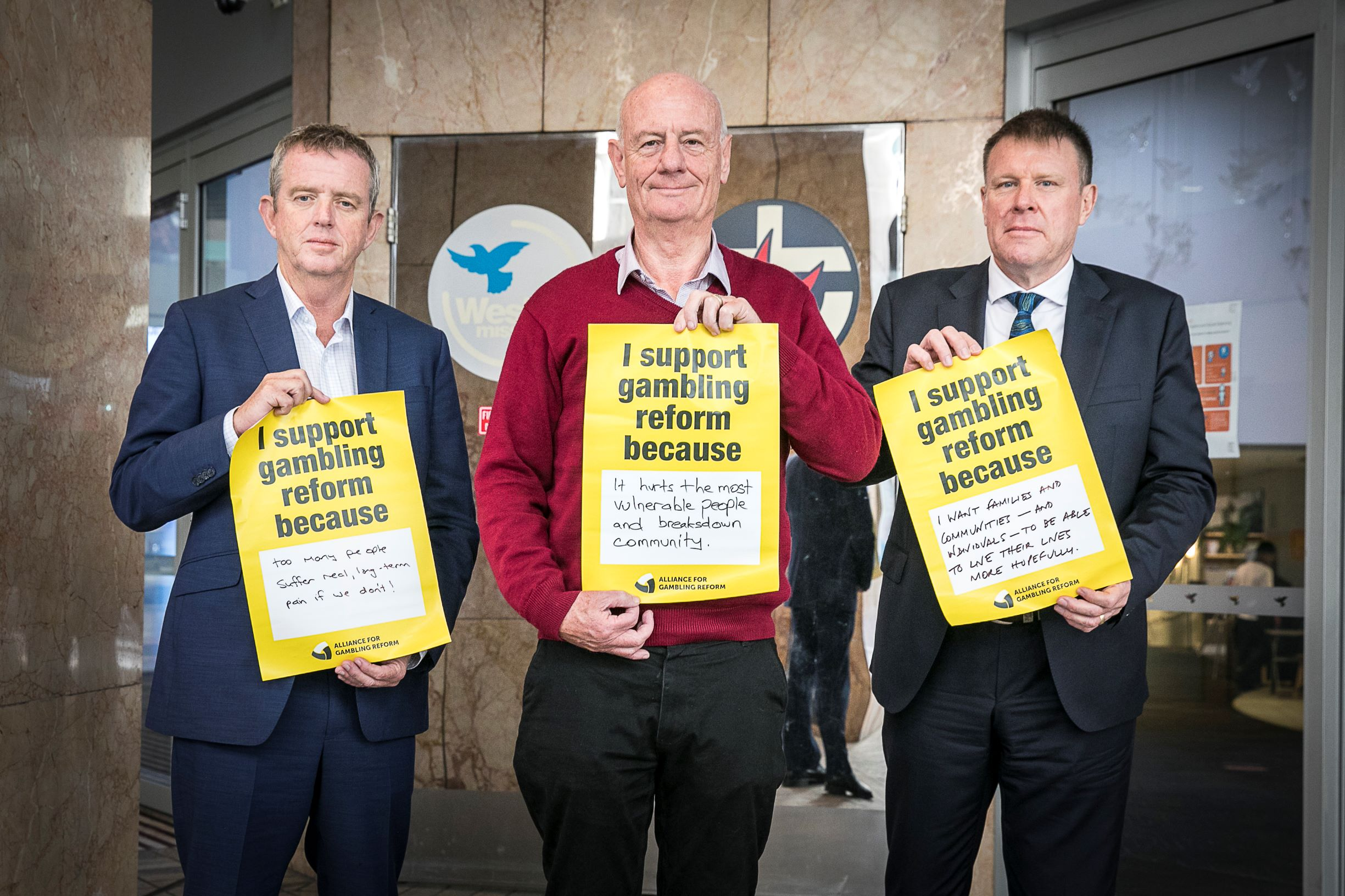 Three men standing holding posters about gambling reform