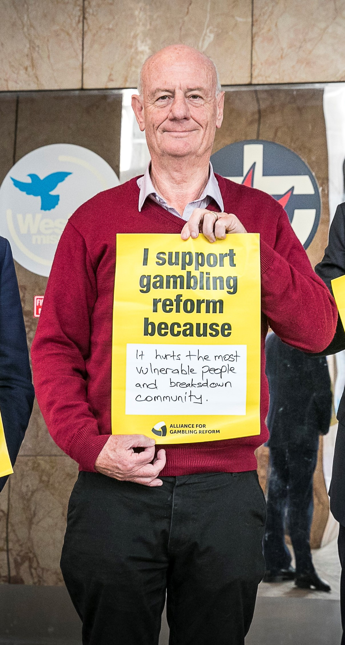 Tim Costello standing holding a gambling reform poster