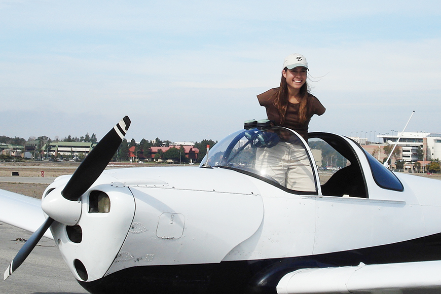 Jessica Cox standing up in airplane cockpit.