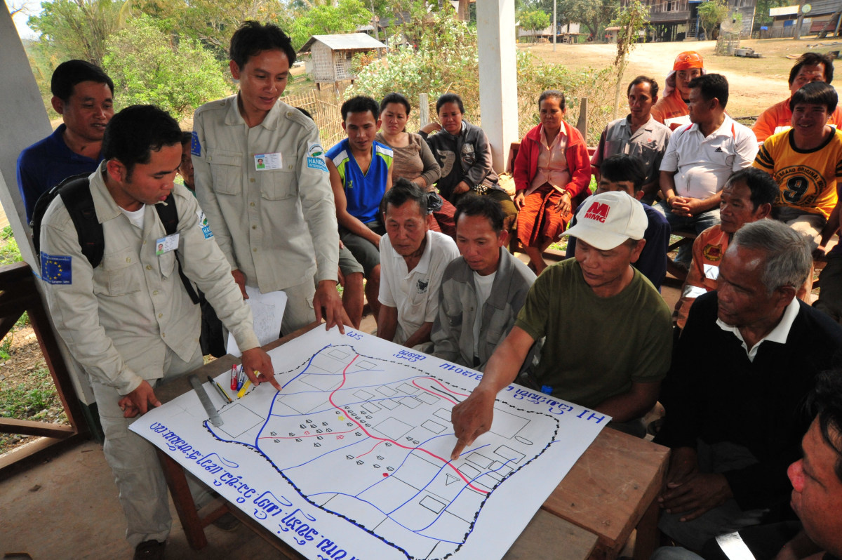 c_Till-Mayer_Handicap-International__Villagers_in_Laos_consult_with_a_demining_team.JPEG