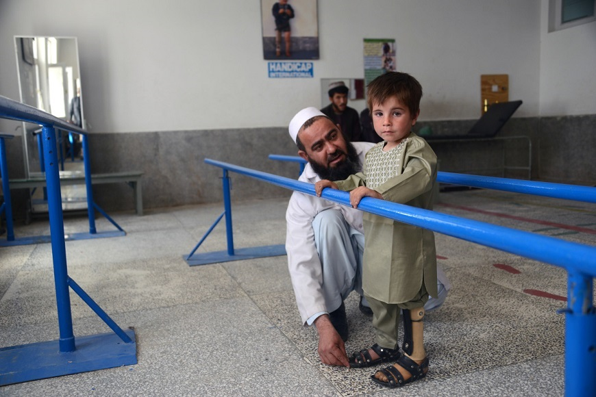 c_Jaweed-Tanveer_Handicap-International__A_young_boy_looks_at_the_camera_as_his_therapist_adjusts_his_prosthetic_limb.jpg