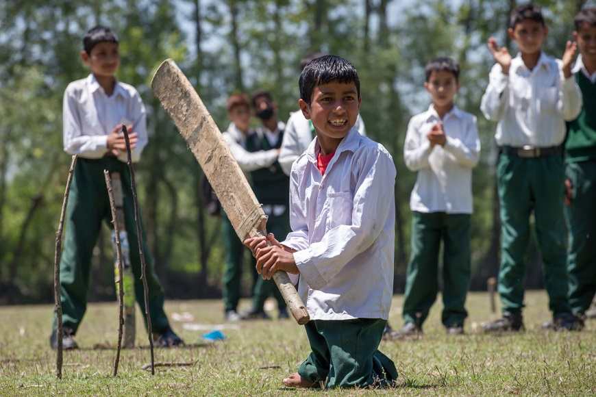 c_L-Veuve_Handicap-International_Sahil_stands_ready_with_a_cricket_bat_surrounded_by_other_children.jpg