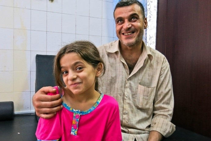 c_E-Fourt_Handicap-International_Safa_and_her_father_Ahmad_as_she_waits_to_be_measured_for_her_new_prostheses.jpg
