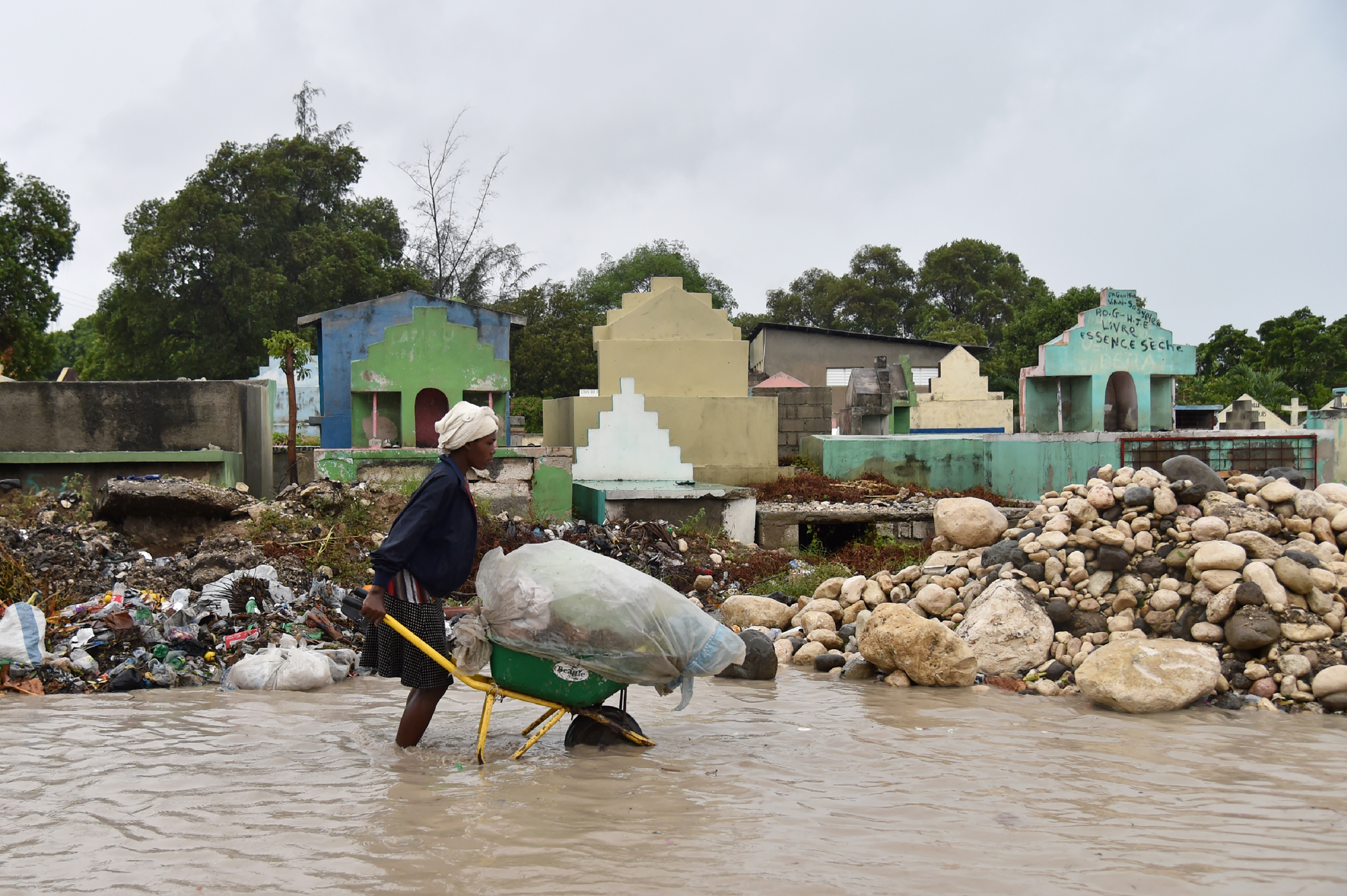 c_Hector-Retamal_AFP__A_woman_pushes_a_wheel_barrel_through_high_waters_in_Haiti.jpeg