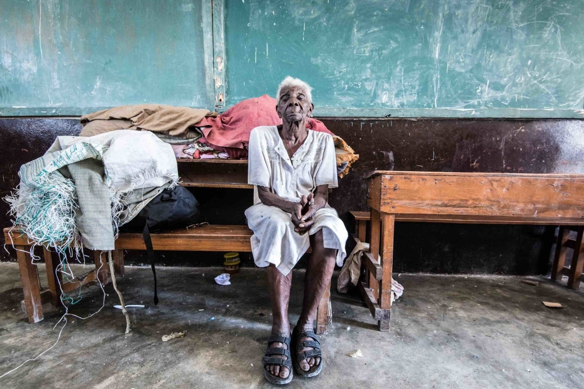 c_Benoit-Almeras_Handicap-International__Haitian_woman_sits_on_a_bench_in_a_local_school_where_she_is_staying_after_Hurricane_Matthew_destroyed_her_home.JPEG