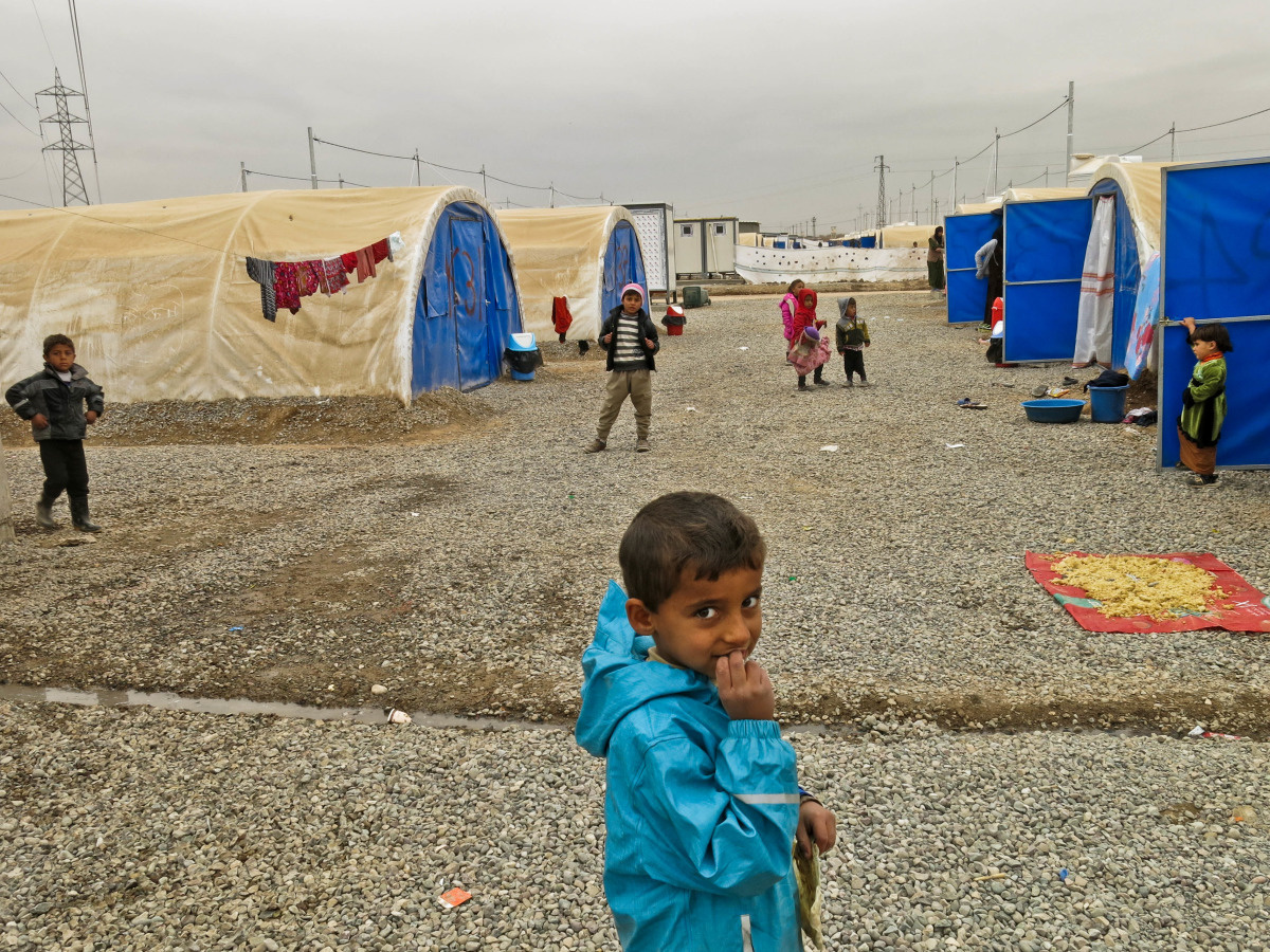c_E-Fourt_Handicap-International__Boy_stands_in_front_of_tents_at_the_Khazer_IDP_camp_in_Iraq.jpg