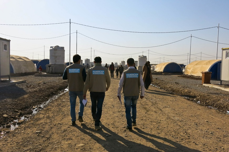 c_E-Fourt_Handicap-International__Three_handicap_international_staffers_walk_down_a_camp_street_in_Iraq.jpg
