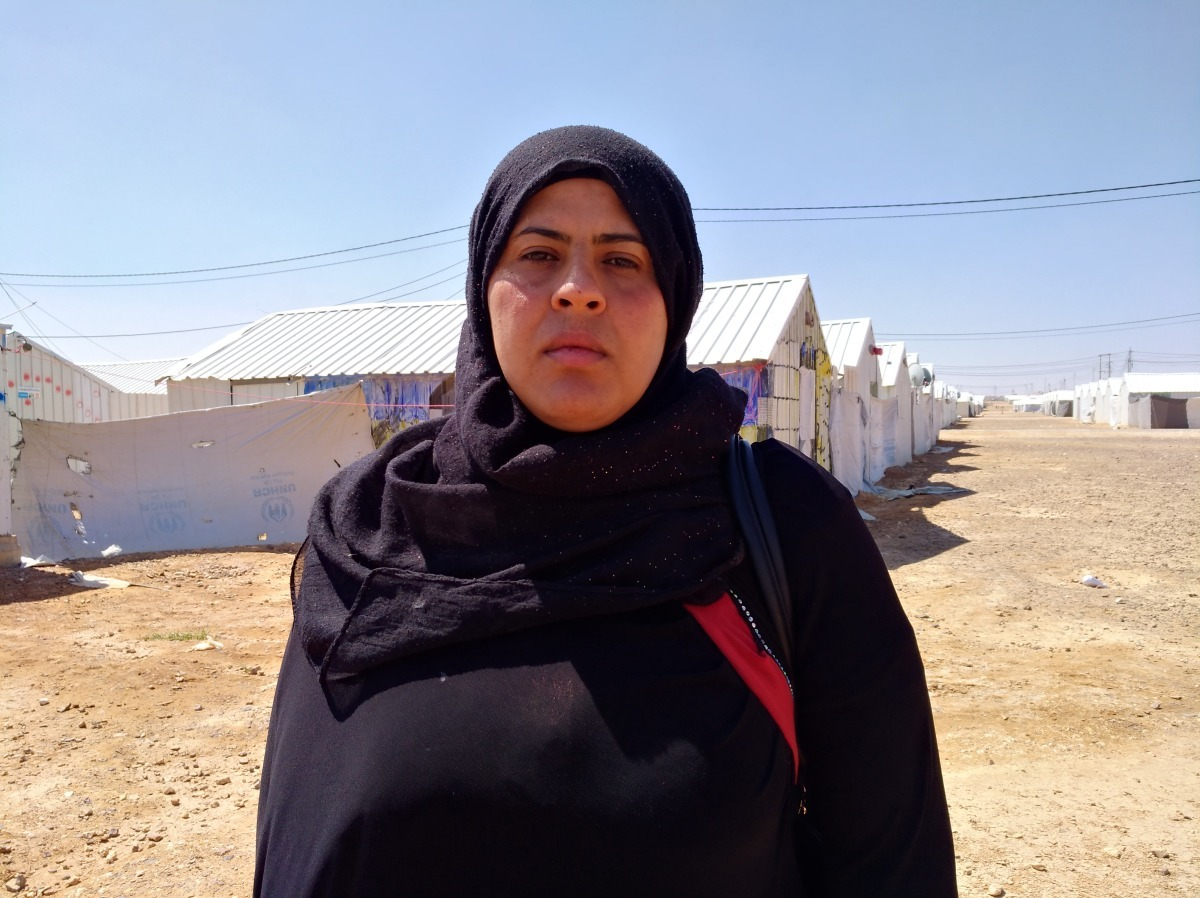A Syrian woman stands and poses for a photo at a refugee camp in Jordan.