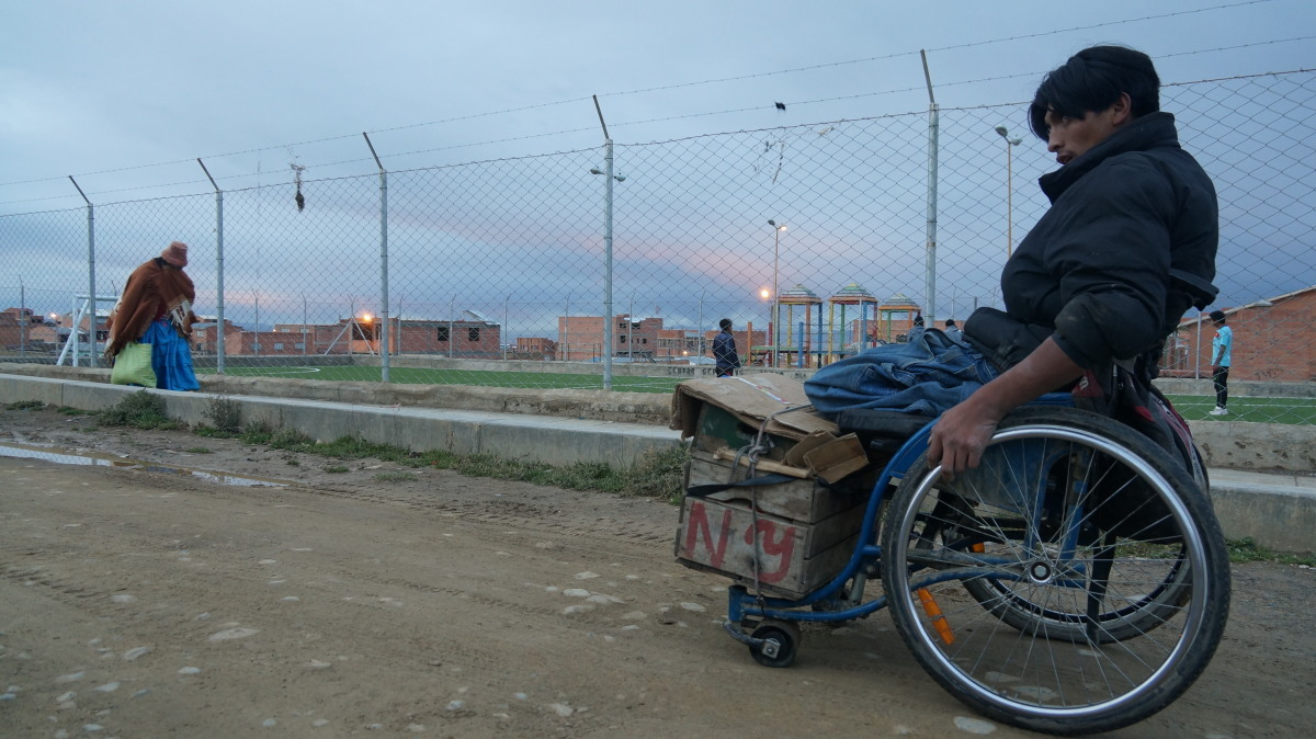 A man in a wheelchair pushes a wooden crate down a path in Bolivia.