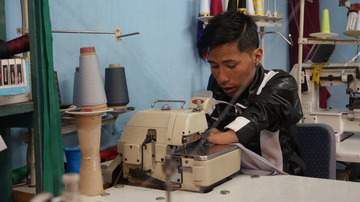 A man with a disability is operating a sewing machine in Bolivia