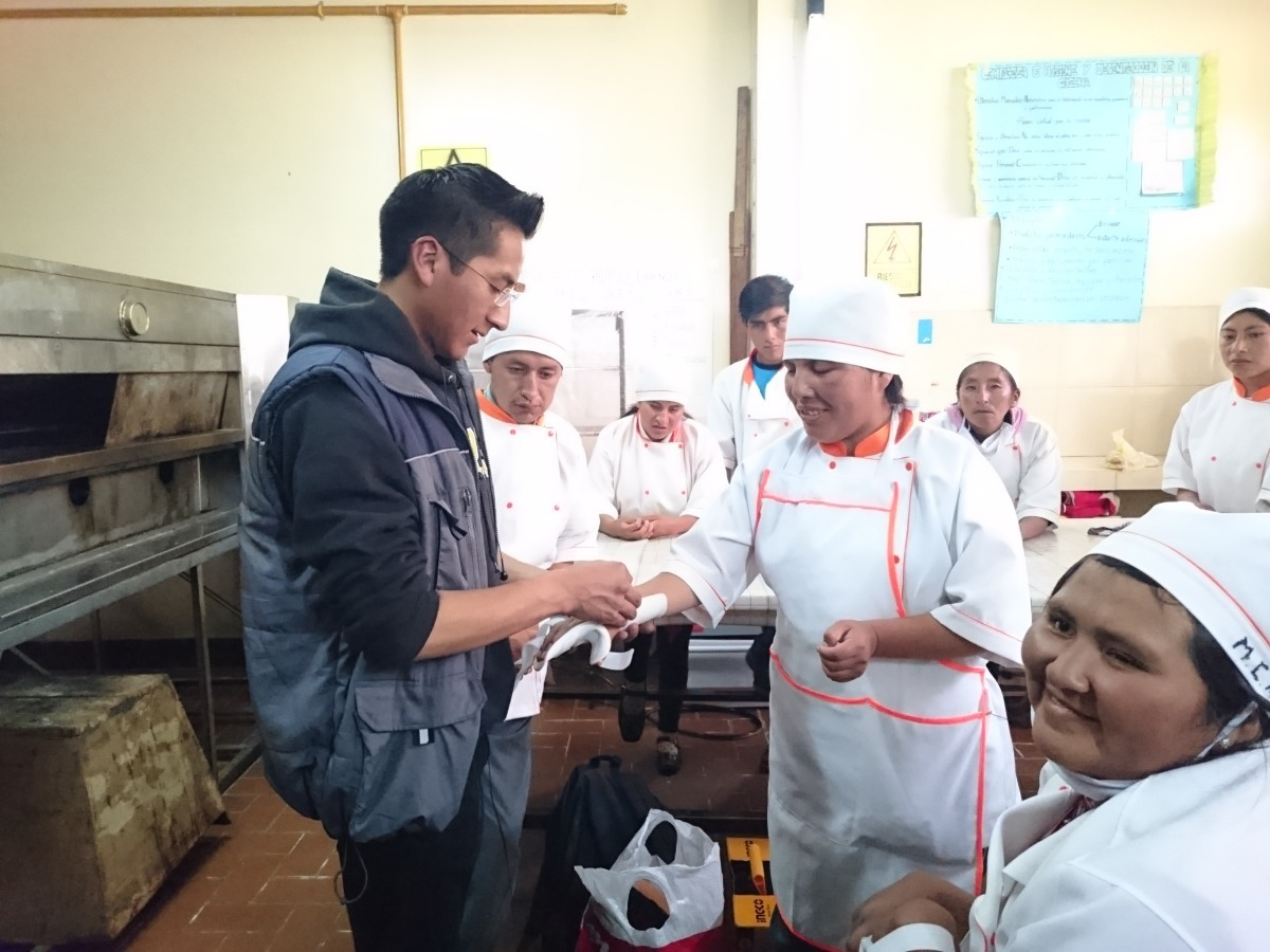 A male student is giving a personalized arm stint to a woman with a disability in Bolivia